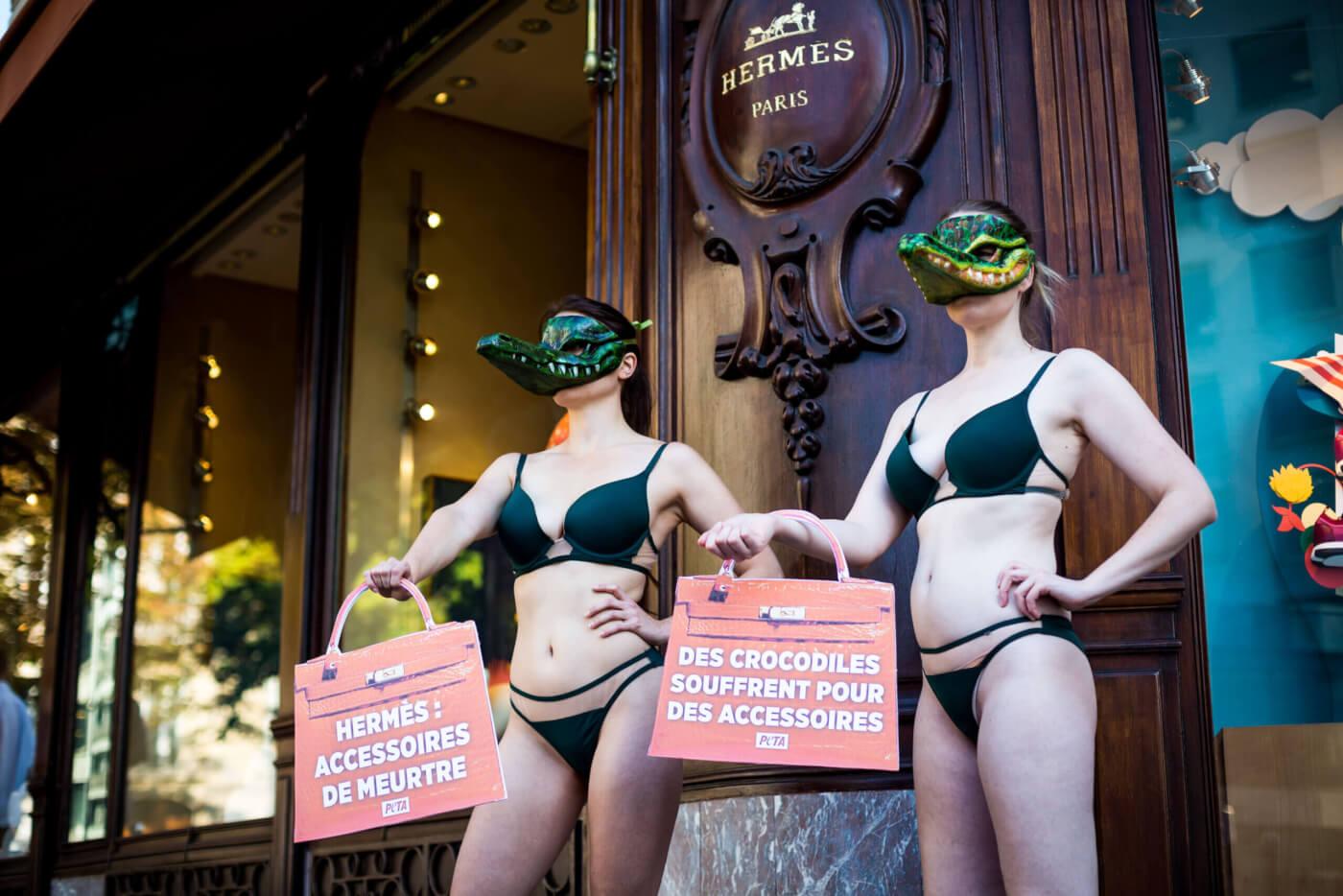 Activists wearing bikinis and crocodile masks protest at Hermès in Paris.