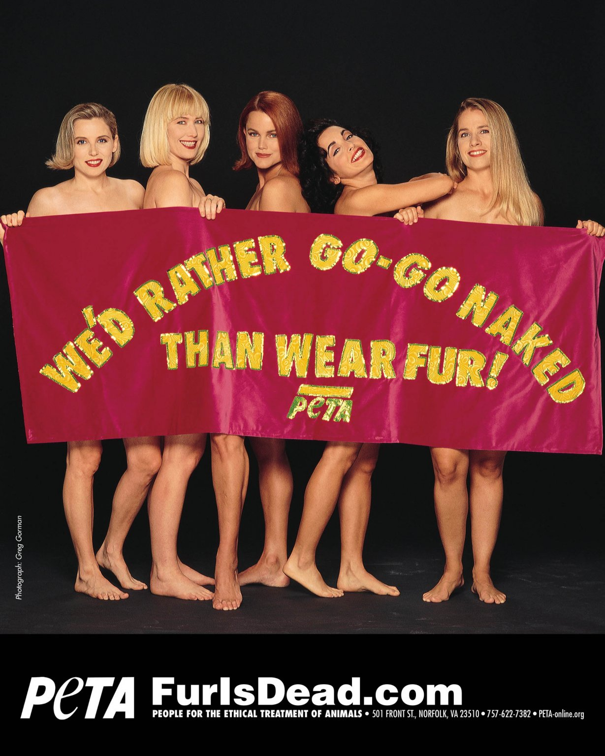"""A photo of The Go Gos behind a banner that reads """"We'd Rather Go-Go Naked Than Wear Fur!"""""""