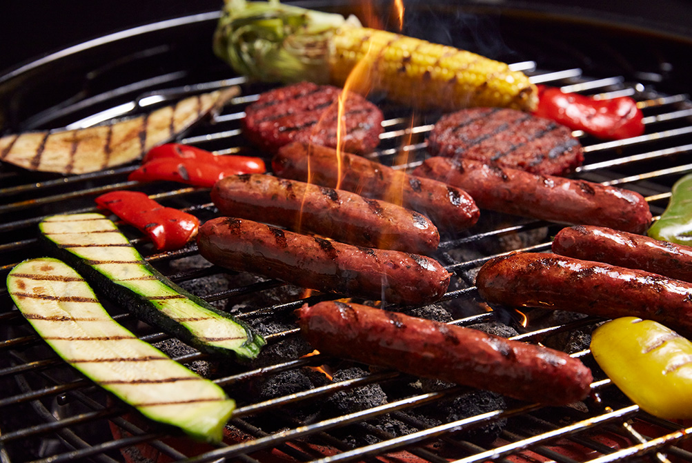 A photo of a vegan BBQ with sausages, burger patties and vegetables.