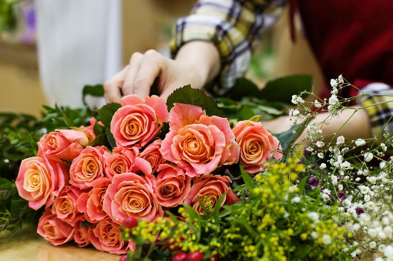 A photo of flowers being arranged on a table.