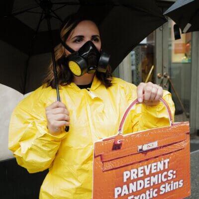 An activist wearing a mask and a hazmat suit.