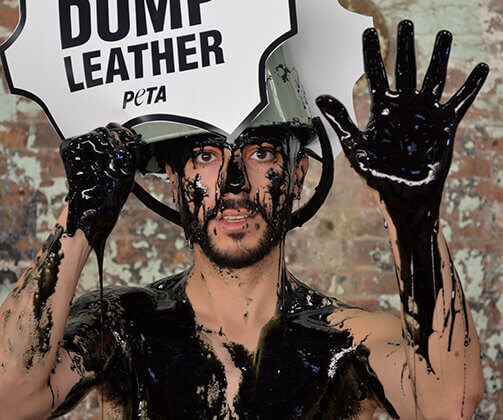 """PETA supporters pour buckets of black """"toxic slime"""" – representing the harmful waste generated by the leather industry – over their heads at Fashion Week."""