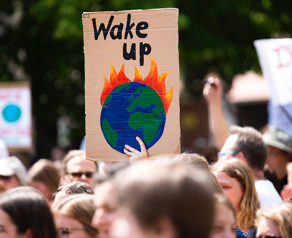 """Image of a poster that says """"Wake Up"""" at a Climate Strike protest."""
